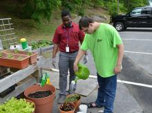 Student watering garden as staff member watches